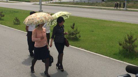 Pyongyang women wear their Sunday best, including ornate umbrellas to shield themselves from the sun.