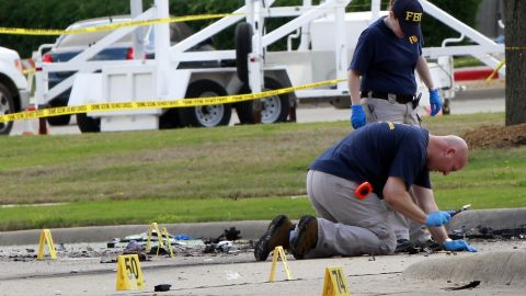 """Investigators work a crime scene before the removal a two bodies outside of the Curtis Culwell Center after a shooting occurred the day before May 04, 2015 in Garland, Texas. During the """"Muhammad Art Exhibit and Cartoon Contest, """" an anti-Islam event, on May 03, Elton Simpson of Phoenix, Arizonia and another man opend fire, wounding a security guard . Police officers shot and killed Simpson at the scene."""