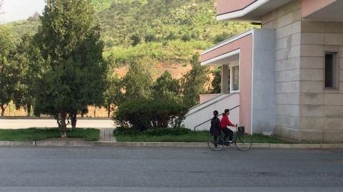 Two women share a bicycle as they head south on a highway leading from Pyongyang to the DMZ.