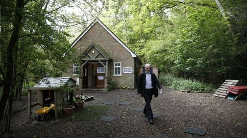 A member of the public leaves a polling station in Mattingley, England.
