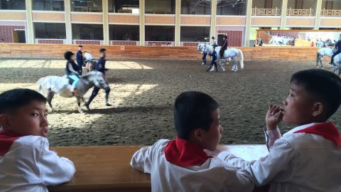 North Korean students watch riding lessons at a new equestrian center designed by Supreme Leader Kim Jong Un. The facility was formerly used for military training.