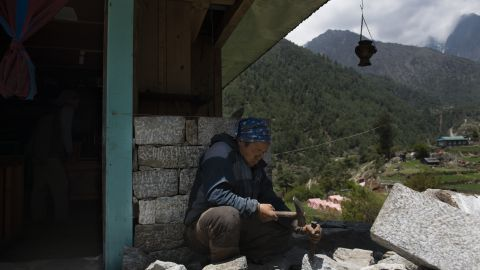 A Sherpa man cuts stone to try rebuilding his damaged house. Many of the houses in this part of Solokhumbu District were built with stone, cement and wood and sustained major damage.