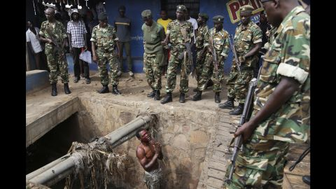 Jean Claude Niyonzima, a suspected member of the ruling party's Imbonerakure youth militia, pleads with soldiers to protect him from a mob of demonstrators after he came out of hiding in a sewer in the Cibitoke  district of Bujumbura, Burundi, Thursday May 7, 2015.  Niyonzima fled from his house into the sewer under a hail of stones thrown by a mob protesting President Pierre Nkurunziza's decision to seek a third term in office. At least one protestor has died in clashed with the widely feared Imbonerakure militias and police, sending scores to the streets seeking revenge.