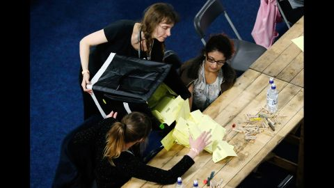 A volunteer empties a ballot box onto a table for votes to be counted in Sheffield, England, on May 8.