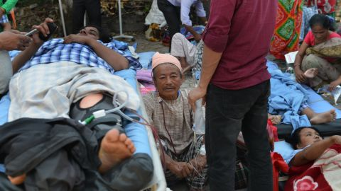 Patients lie on stretchers in an open area after being carried out of a hospital building on May 12.