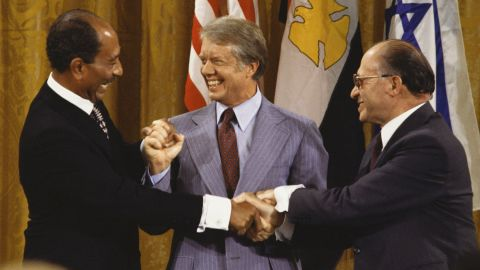 Egyptian President Anwar Sadat, left, joins hands with Israeli Prime Minister Menachem Begin, right, on September 18, 1978, after the Camp David Accords were signed in Maryland. After 12 days of secret meetings, the two sides agreed upon a step toward peace. U.S. President Jimmy Carter, center, personally led the lengthy negotiations and discussions between the two parties.