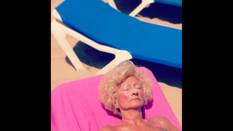 """A woman sunbathes in the Spanish town of Benidorm, a beach haven for many working-class tourists and pensioners from northern Europe. """"Scenes of Radioactive Life"""" is Maria Moldes' two-year photographic ode to Benidorm, highlighting the extravagance of the place and its characters. """"It is an endless source of images,"""" she said."""