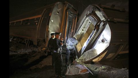 Police stand between two overturned train cars on Tuesday, May 12.