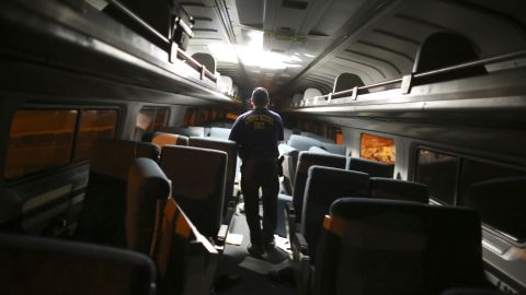 A crime scene investigator looks inside a train car.