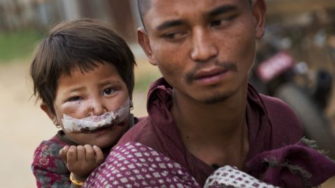 A man carries his child to a camp for displaced people in Chautara on May 13.