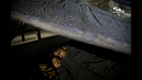A family sleeps in an open space sheltered by plastic sheets in Kathmandu, Nepal, on Tuesday, May 12.