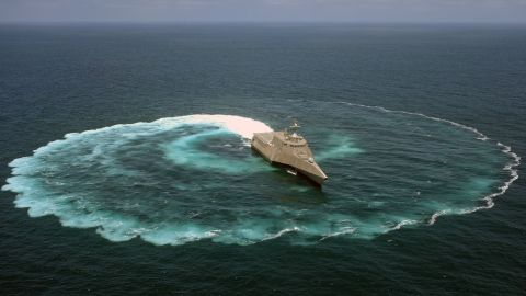 """The littoral combat ship USS Independence (LCS 2) demonstrates its maneuvering capabilities in the Pacific Ocean off the coast of San Diego. LCS crew commander John Kochendorfer described the ships as """"a military jet ski with a flight deck and a gun."""""""