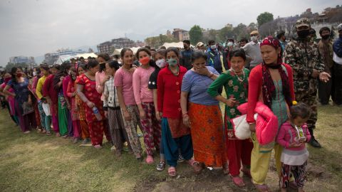 Nepalese women and children wait in line to receive food distributed by a non-government organization in the center of Kathmandu