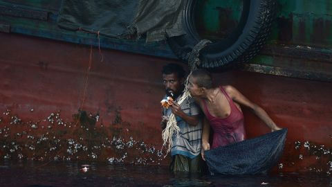 A Rohingya migrant eats food dropped by a Thai army helicopter after he swam to collect the supplies at sea. Malaysia, meanwhile, is processing more than 1,000 recently arrived migrants.