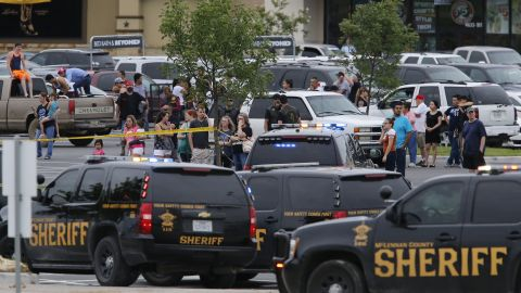 People at the Central Texas MarketPlace watch a crime scene near the parking lot of a Twin Peaks restaurant on Sunday, May 17 in Waco, Texas.