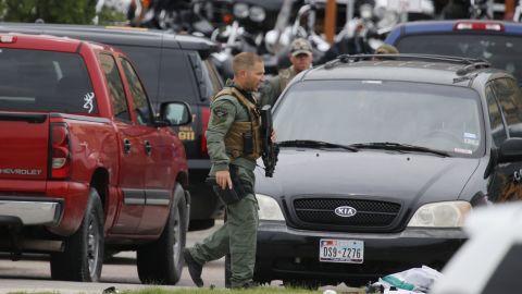 A law enforcement officer walks past debris near the parking lot of the restaurant.