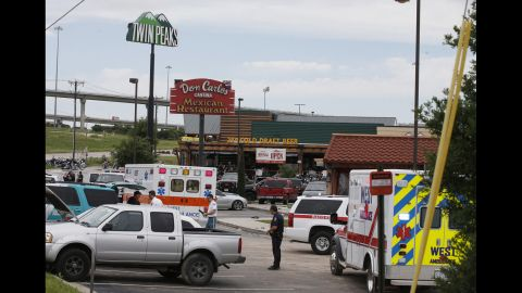 Emergency vehicles and members of law enforcement gather near the scene of the shooting.