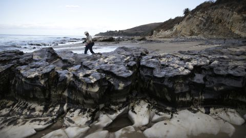 A member of the Bureau of Land Management walks past rocks covered in oil on May 21.