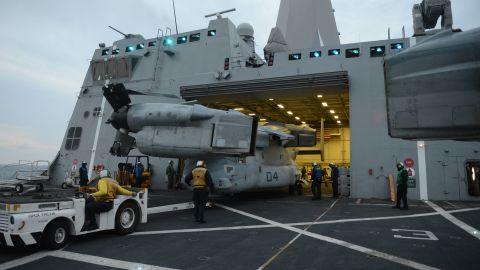 Sailors aboard the amphibious transport dock ship USS Mesa Verde (LPD 19) stow an MV-22 Osprey in the hangar bay.