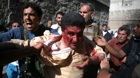 Rebel fighters with the Free Syrian Army capture a police officer in Aleppo, Syria, who they believed to be pro-regime militiaman on July 31, 2012. Dozens of officers were reportedly killed as rebels seized police stations in the city.