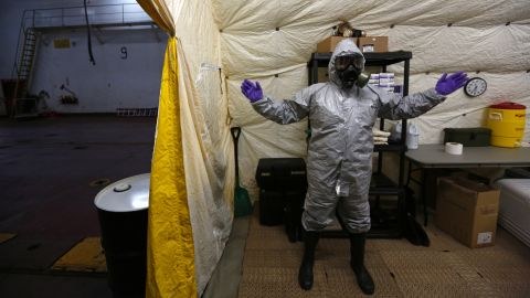 A US ship staff member wears personal protective equipment at a naval airbase in Rota, Spain, on April 10, 2014. A former container vessel was fitted out with at least $10 million of gear to let it take on about 560 metric tons of Syria's most dangerous chemical agents and sail them out to sea, officials said.