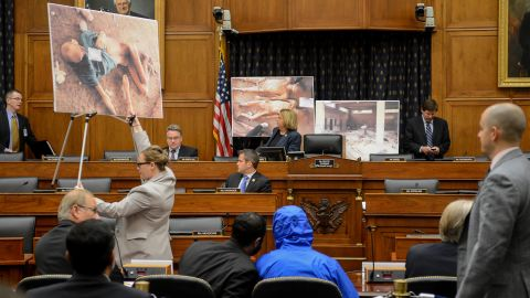 """Photographs of victims of the Assad regime are displayed as a Syrian army defector known as """"Caesar,"""" center, appears in disguise to speak before the House Foreign Affairs Committee in Washington. The July 31, 2014, briefing was called """"Assad's Killing Machine Exposed: Implications for U.S. Policy."""" Caesar, apparently a witness to the regime's brutality, smuggled more than 50,000 photographs depicting the torture and execution of more than 10,000 dissidents. CNN cannot independently confirm the authenticity of the photos, documents and testimony referenced in the report."""