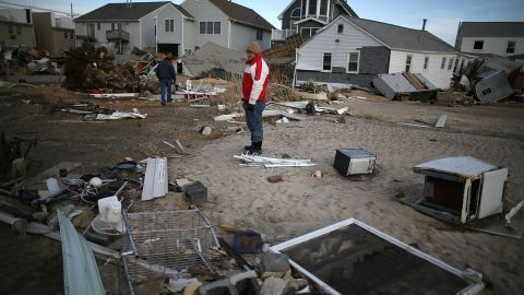 """<strong>Sandy, 2012:</strong> It technically lost its hurricane status shortly before striking New Jersey, but its gigantic size -- it covered 1.8 million square miles at landfall -- sent devastating storm surges to the coast. Here, a man looks for pieces of his beach house after <a href=""""http://www.cnn.com/2013/07/13/world/americas/hurricane-sandy-fast-facts/"""">Sandy </a>demolished it in Seaside Heights, New Jersey. With 72 directly killed in eight states, this was the most deadly tropical cyclone outside the South since 1972's Hurricane Agnes. At least 650,000 U.S. homes were damaged or destroyed in the U.S."""