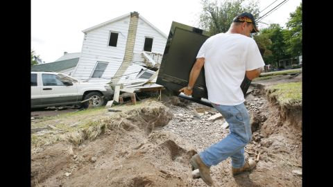 """<strong>Irene, 2011:</strong> After hitting North Carolina, <a href=""""http://www.nhc.noaa.gov/data/tcr/AL092011_Irene.pdf"""" target=""""_blank"""" target=""""_blank"""">Irene</a> did most of its damage in the way of heavy rain and flooding in New York and New England. In southern Vermont alone, nearly 2,400 roads were damaged or destroyed, NOAA says. Here, Tony Carr carries a TV set September 1 from his home, which was destroyed by Irene-related floods in Prattsville, New York."""