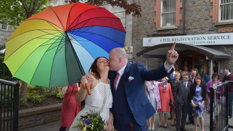 """Newly married couple Anne and Vincent Fox kiss in Dublin on Friday, May 22, under a rainbow umbrella, showing their support for the """"yes"""" side in the same-sex marriage referendum.<br />"""