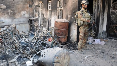 An Iraqi security forces member stands outside a burned house during fighting with anti-government forces Thursday in Ramadi, west of Baghdad.