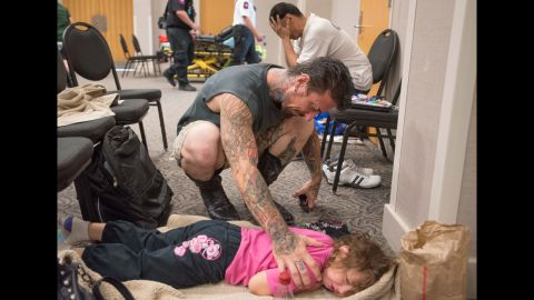 David Barry consoles his 5-year-old daughter, Marley, while she tries to sleep in a flood evacuee room created at the San Marcos Activity Center on May 24.