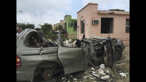 People stand near a destroyed vehicle in the city.
