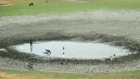 Fishermen attempt to catch fish in a shrunken pond in Phaphamau, India, on Tuesday, May 26.