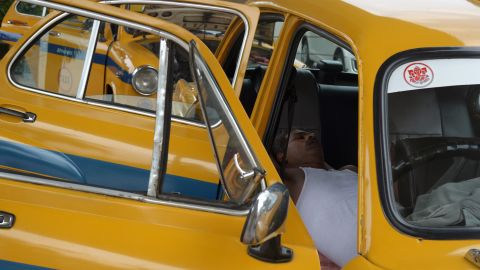 A taxi driver rests in his parked car in Kolkata, India, on Monday, May 25.