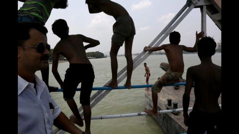People in Kolkata flock to the murky waters of the Hooghly River for a cooling dip on Friday, May 15.