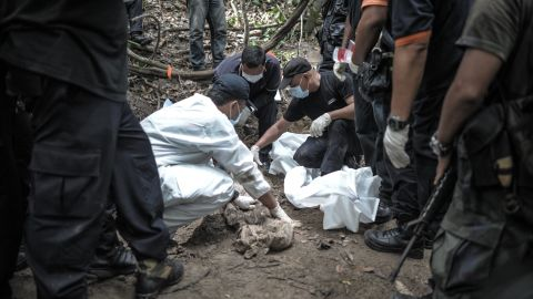 A Royal Malaysian Police forensic team handles exhumed human remains in a jungle at Bukit Wang Burma in the Malaysian northern state of Perlis, which borders Thailand, on May 26, 2015. Malaysian police May 26 began the grisly job of exhuming dozens of graves found in a series of remote human-trafficking camps along the Thai border in the latest grim turn in the region's migrant crisis. Police said May 25 they had found 139 grave sites and 28 abandoned detention camps used by people-smugglers and capable of housing hundreds, laying bare the grim extent of the region's migrant crisis. AFP PHOTO / MOHD RASFANMOHD RASFAN/AFP/Getty Images