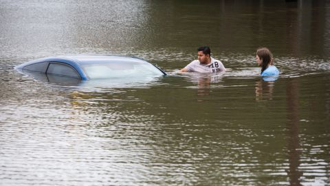 Roberto Salas, left, and Lewis Sternhagen check on a flooded car in Houston on May 26.