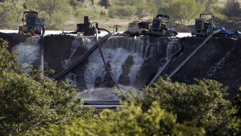 Workers in Midlothian, Texas, try to relieve pressure from the dam at Padera Lake on May 27.