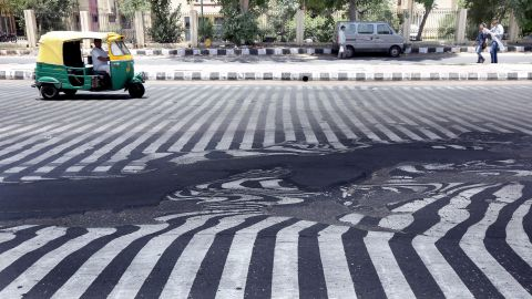 Road markings appear distorted as asphalt starts to melt because of the high temperature in New Delhi on May 27.