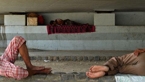 Men sleep in the shade under a bridge in New Delhi on May 27.