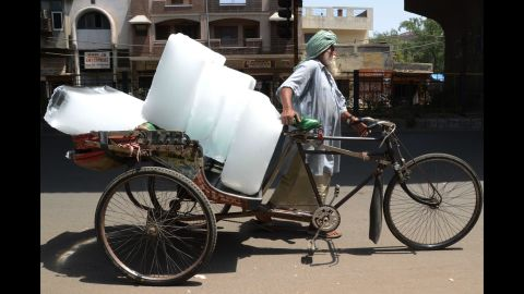 A worker in Amritsar, India, uses a rickshaw to transport ice from a factory on Wednesday, May 27.