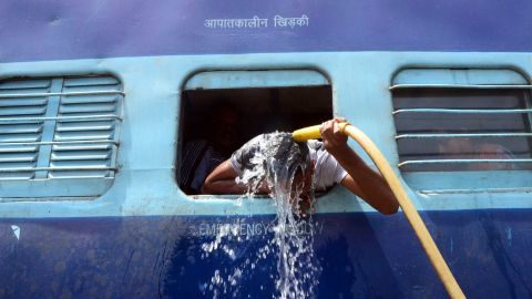 A commuter uses a train's hose to cool down at the railway station in Allahabad on Sunday, May 24.