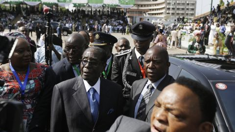 Zimbabwean President Robert Mugabe, in the blue tie, arrives for the inauguration.