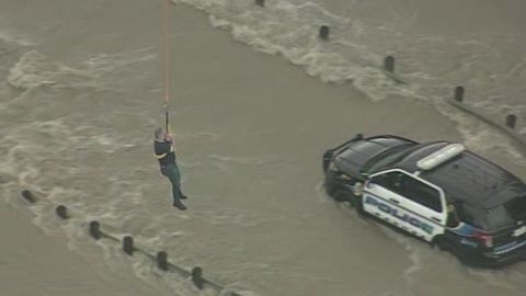 A police officer is plucked from his patrol car after a flash flood stranded him.