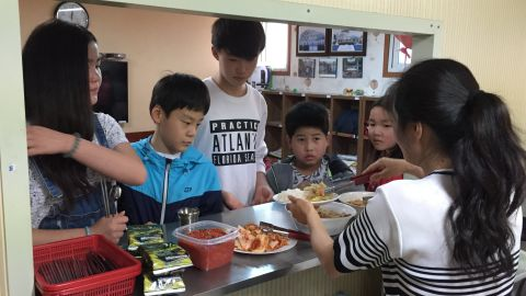 Children queue for lunch at the Kumgang school in Seoul.