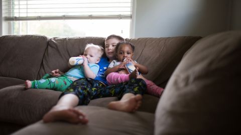 """Older brother Ethan was able to spend time with his siblings, Isaac and Ellie, during feedings. """"It was a team effort,"""" Whitman said of bottle feeding."""