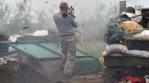 A Ukrainian serviceman fires a grenade launcher on the front lines near Donetsk on Saturday, May 30.