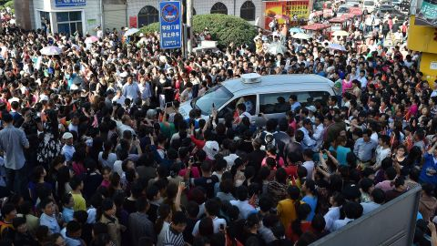 Parents crowd a police car outside Maotanchang High School as students leave to sit the 2015 college entrance exam.