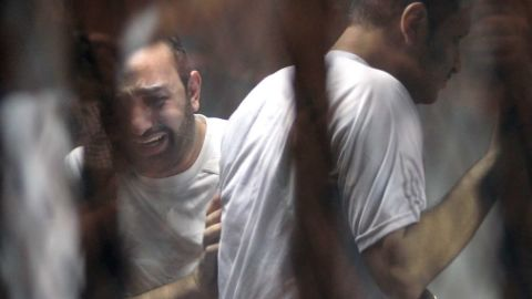 Egyptian defendants react behind bars after the verdict in their retrial over a 2012 stadium riot in the canal city of Port Said that left 74 people dead, on June 9, 2015 in a court in the Egyptian capital, Cairo. The court upheld death sentences against 11 football fans over the riot which broke out when fans of home team Al-Masry and Cairo's Al-Ahly clashed after a premier league match between the two clubs.
