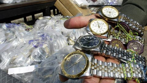 An unidentified Thai customs officer shows counterfeit Rolex watches confiscated in different raids during a display at the customs house in Bangkok, 11 March 2004. Thai authorities displayed different counterfeit items smuggled into the kingdom from overseas to show Thailand's commitment to halting the proliferation of fake goods and violations of intellectual property. AFP PHOTO/ Saeed KHAN (Photo credit should read SAEED KHAN/AFP/Getty Images)